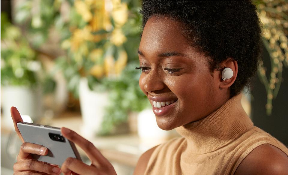 Женщина в наушниках WF-1000XM4 просматривает медиаданные на смартфоне