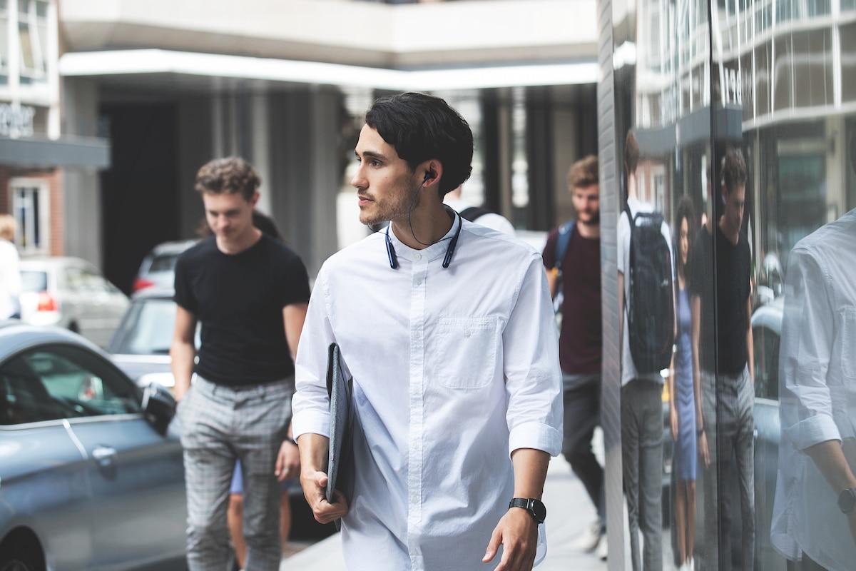Изображение человека, идущего по улице в наушниках с включенным режимом окружающего звука