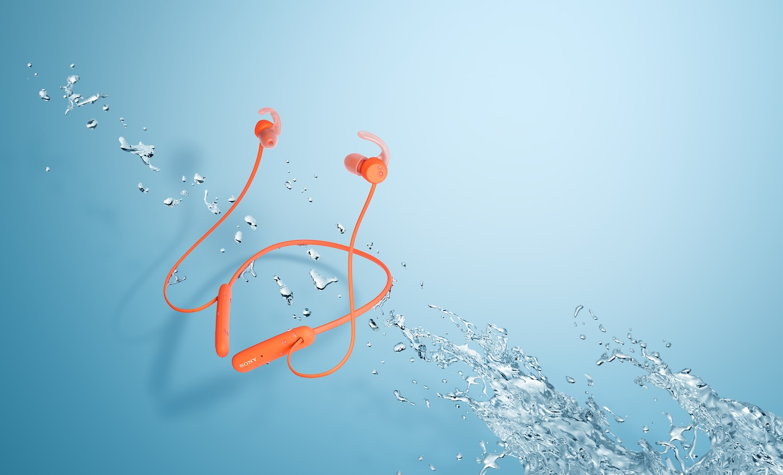 Красные наушники WI-SP510 в брызгах воды
