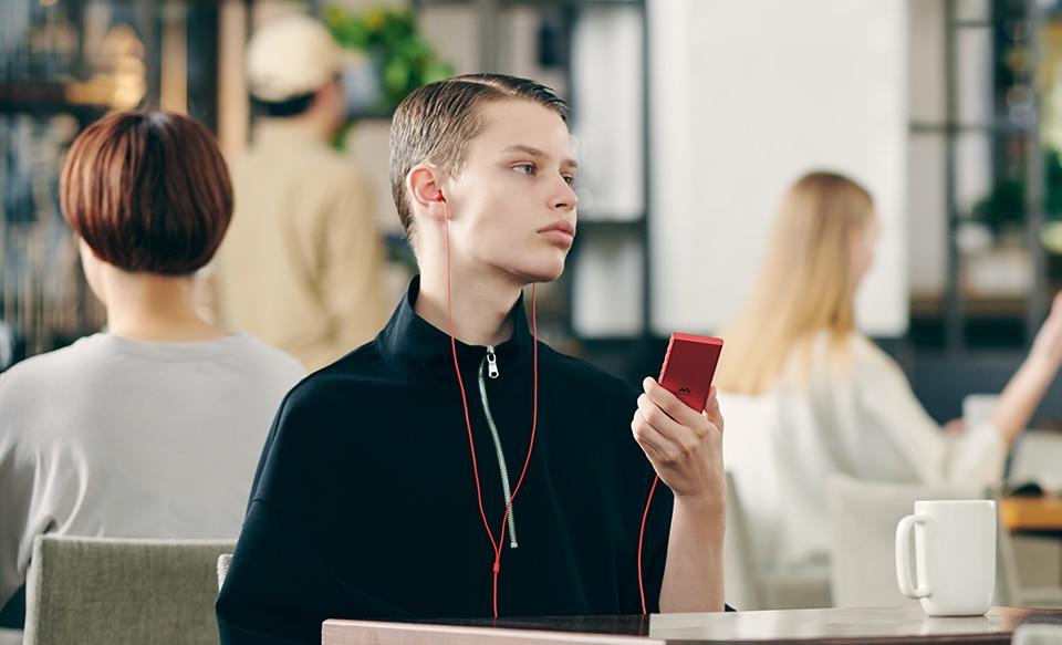 Изображение мужчины в кафе, который слушает музыку с плеера NW-A100 Walkman