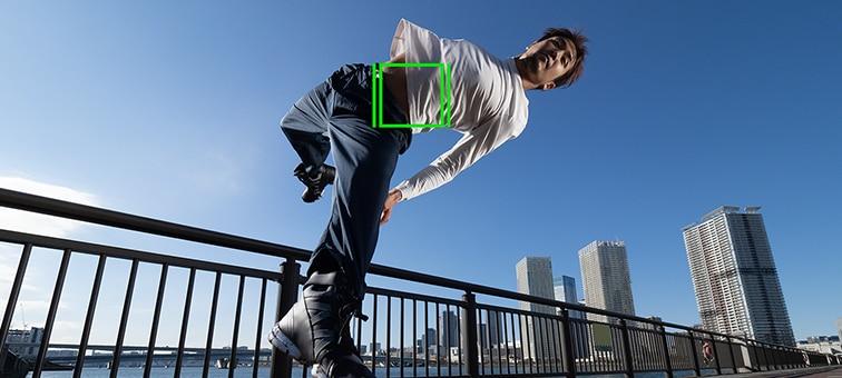 Мужчина прыгает на мосту, а посредине его тела виден зеленый квадрат автофокусировки