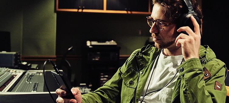 Изображение человека, который слушает музыку в наушниках на Xperia 1 III в студии звукозаписи