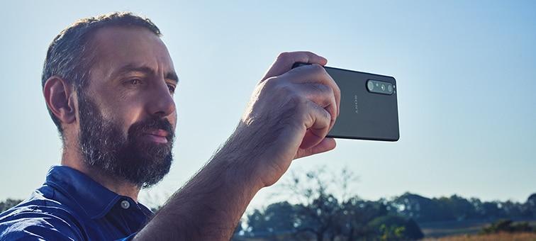 Изображение человека, который ведет съемку на Xperia 1 III на улице