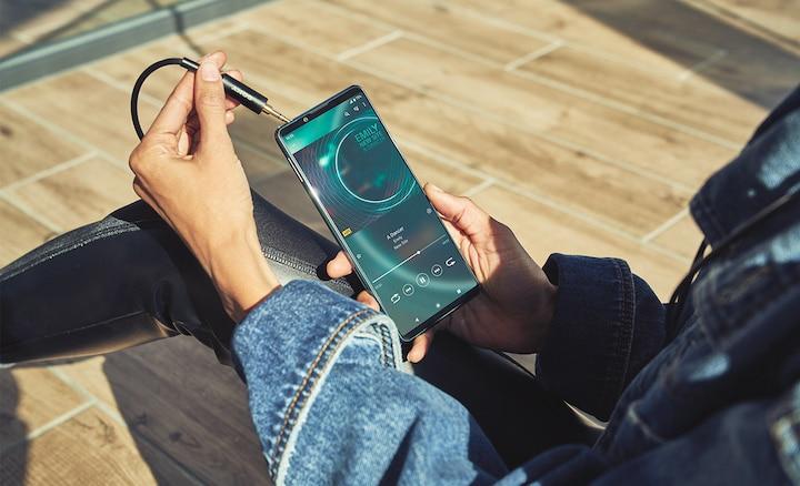 Человек подключает проводные наушники к Xperia 5 III через аудиоразъем 3,5 мм