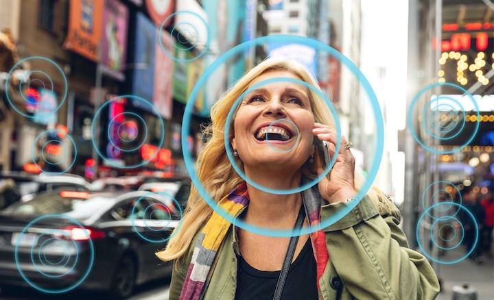 Женщина на оживленной улице демонстрирует, как технология Voice Zoom2 улучшает слышимость речи