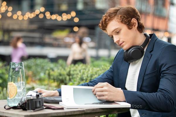 Человек в кафе с наушниками WH-1000XM4 на шее