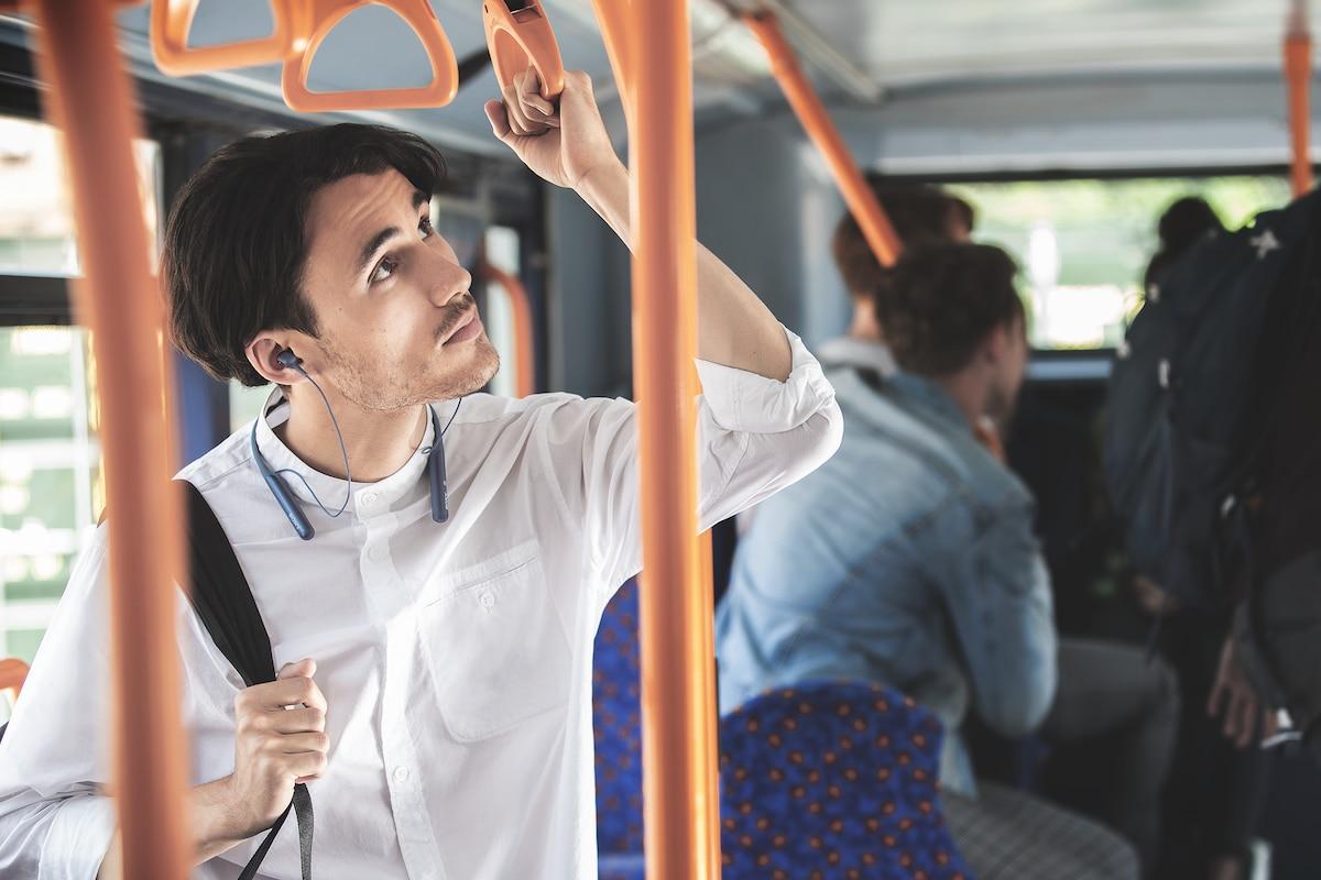 Изображение пассажира в наушниках с включенным режимом окружающего звука, слушающего объявление в автобусе