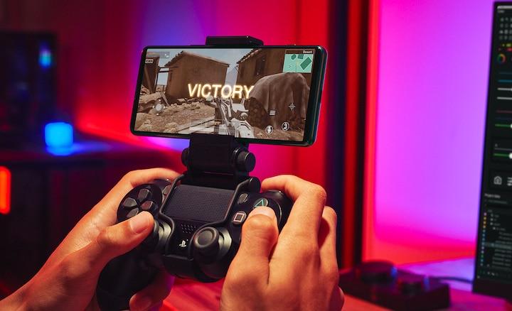 Человек с контроллером Dualshock играет на Xperia 5 III