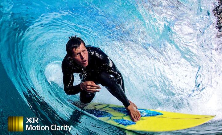 Четкое детализированное изображение серфера, покоряющего волну