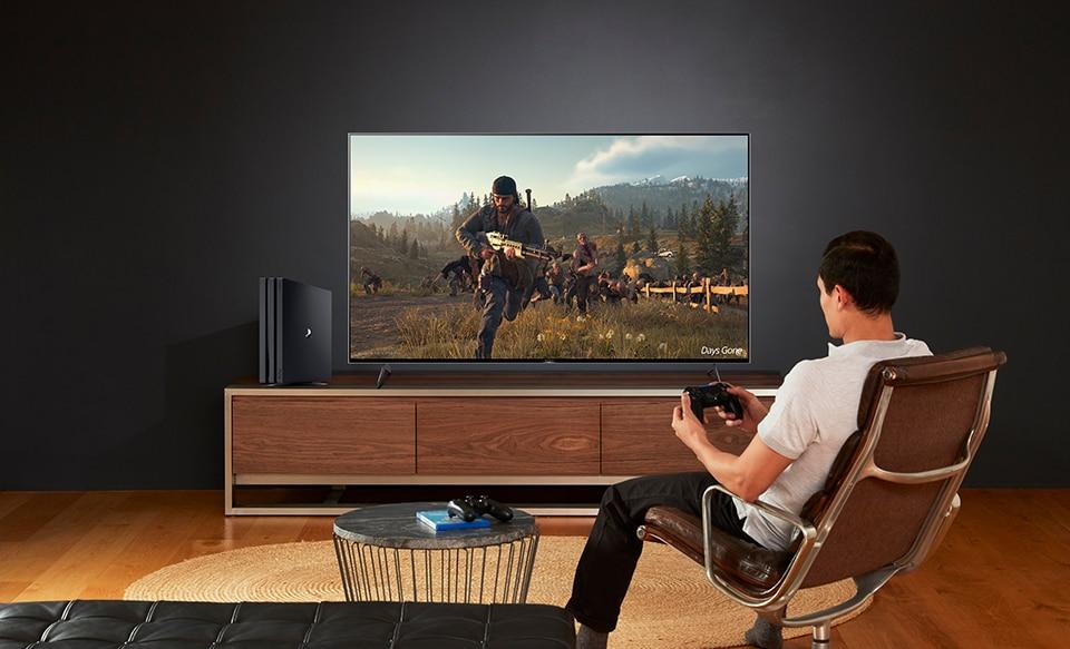 Мужчина играет в игры на телевизоре BRAVIA