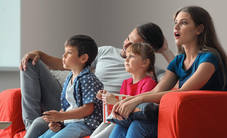 Семья на диване смотрит телевизор