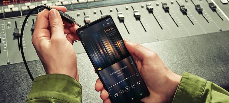 Изображение человека, подключающего Xperia 1 III к микшеру через аудиоразъем 3,5 мм